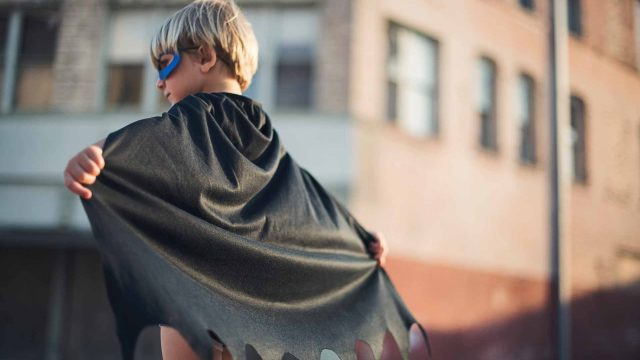 A child with a superhero cape representing 4 qualities of an effective leader