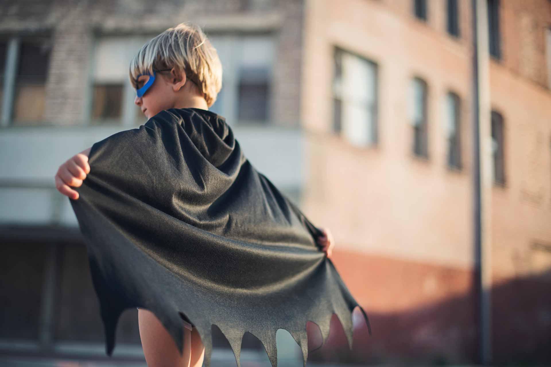 Un niño con capa de superheroe representando 4 cualidades de un líder efectivo